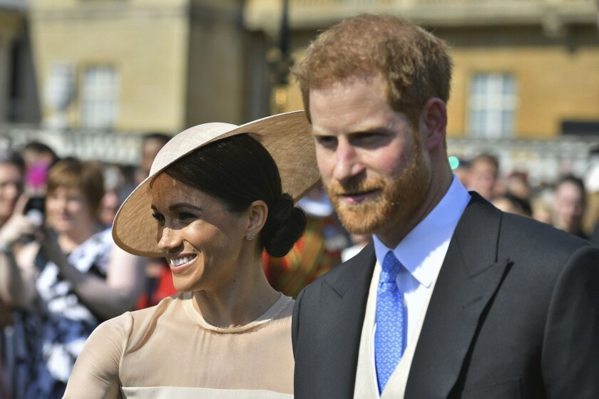 Meghan, the duchess of Sussex, walks with her husband, Prince Harry, as they attend a garden party at Buckingham Palace in London on May 22, 2018.