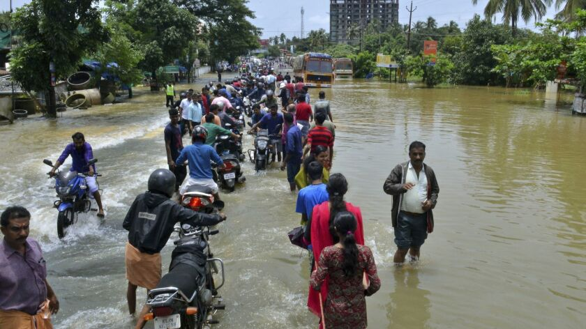 People move past a flooded road in Thrissur, in the southern Indian state of Kerala, Friday, Aug. 17