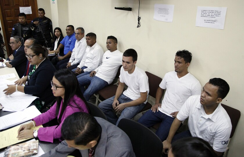 FILE - In this Oct. 15, 2018 file photo, men accused in the murder of Honduran indigenous and environmental rights activist Berta Caceres sit in the courtroom in Tegucigalpa, Honduras. A Honduran court has sentenced seven people convicted of participating in the 2016 murder of Caceres to prison terms of up to 50 years. The court announced the sentences Monday, Dec. 2, 2019. (AP Photo/Fernando Antonio, File)