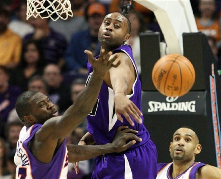 Sacramento Kings' Kenny Thomas, center, reaches for the ball along with Phoenix Suns' Jason Richardson, left, as Suns' Grant Hill looks on during the second quarter of an NBA basketball game in Phoenix, Saturday, Dec. 5, 2009. (AP Photo/Aaron J. Latham)