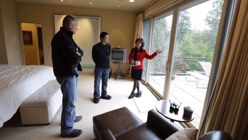 Real estate agent Janie Lee, right, shows a home in Washington state to Hongbin Wei, center, of Beijing, in 2014. In the 12 months that ended in March, international buyers purchased a record number of U.S. homes, according to a new survey.