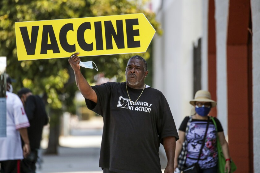 """A man in a """"Mothers in Action"""" T-shirt holds an arrow-shaped sign reading """"Vaccine"""""""