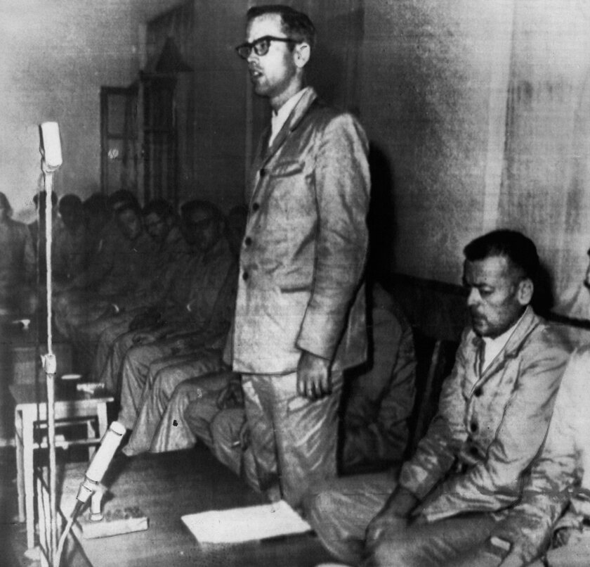 Lt. Edward Murphy, standing, and Cmdr. Lloyd Bucher, seated to his left, during their captivity.
