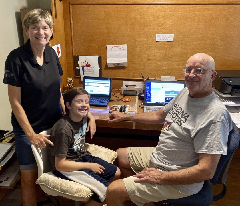 This image released by Bill Hill shows Mary Hill, left, and her husband Bill, right, with their 8-year-old grandson in suburban Phoenix. The 72-year-old Bill, a former college sports administrator, and 70-year-old Mary, who worked as a nurse practitioner, volunteered to keep Will five days a week and oversee distance learning after their son and daughter-in-law were required to report in person to the school where they teach. (Bill Hill via AP)
