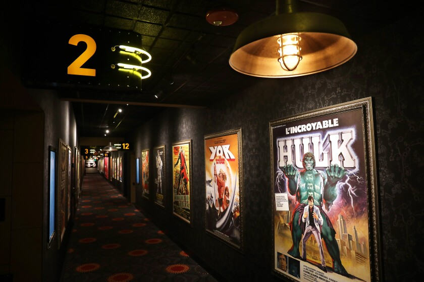 A hallway filled with vintage movie posters from around the world connects the theaters at the Alamo Drafthouse LA