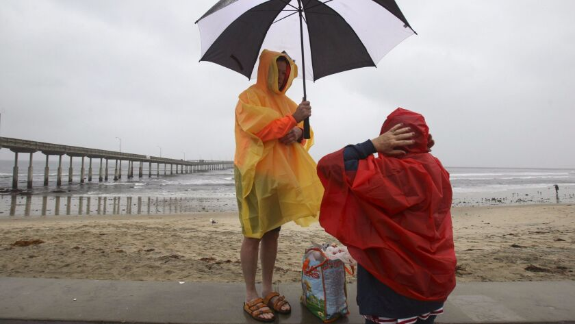 Amid rainy conditions, Caren Hare and Debbie Olds prepare to go on a walk at Ocean Beach on Dec. 31, 2016.