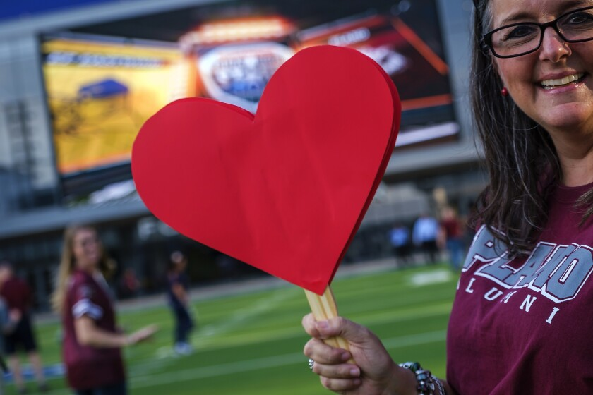 Plano High alumnus Suzanne Wilson arrives with cut-out hearts before a high school football game against El Paso Eastwood on Sept. 5.