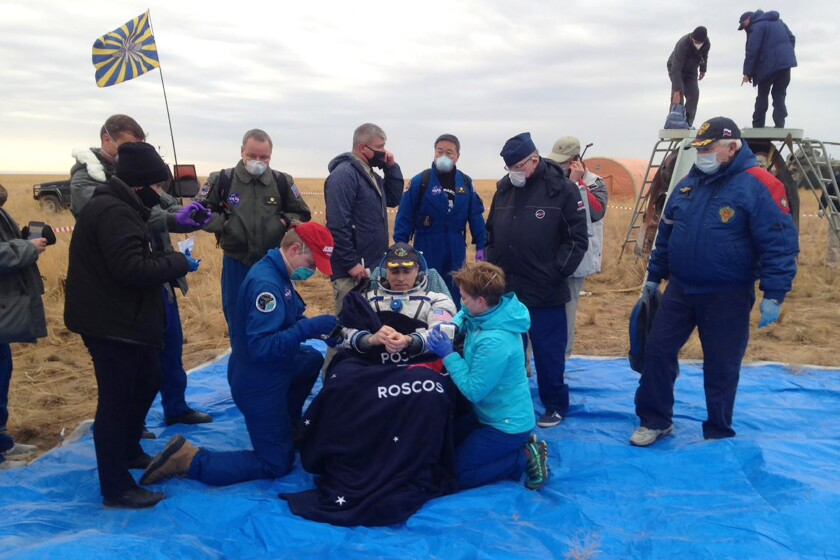 In this photo released by Roscosmos Space Agency, NASA astronaut Chris Cassidy sits in a chair shortly after landing near town of Dzhezkazgan, Kazakhstan, Thursday, Oct. 22, 2020. The Soyuz MS-16 capsule carrying Cassidy and Roscosmos' Anatoly Ivanishin and Ivan Vagner landed on the steppes of Kazakhstan southeast of the town of Dzhezkazgan on Thursday. After a brief medical checkup, the three will be taken by helicopters to Dzhezkazgan from where they will depart home. (Roscosmos Space Agency, via AP)