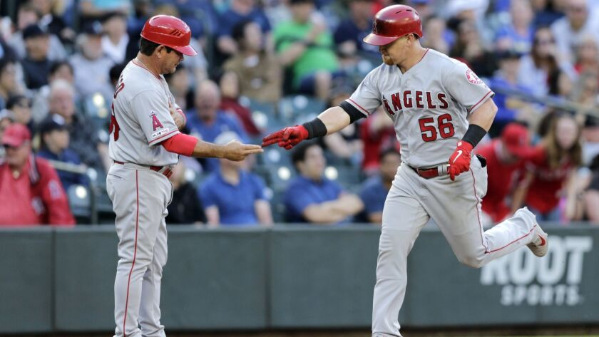 Los Angeles Angels' Kole Calhoun is congratulated by third base coach Mike Gallego after hitting a g