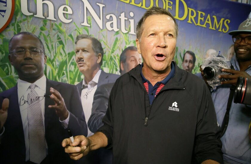 Republican presidential candidate, Ohio Gov. John Kasich reacts after drawing a mustache on his photo on display in the Republican Party of Iowa booth during a visit to the Iowa State Fair, Tuesday, Aug. 18, 2015, in Des Moines, Iowa. (AP Photo/Charlie Neibergall)