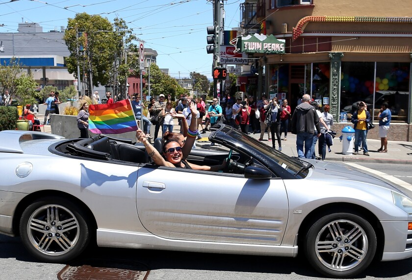 Same-sex marriage supporters wave pride flags from a car as they drive by Market and Castro streets in San Francisco on Wednesday.