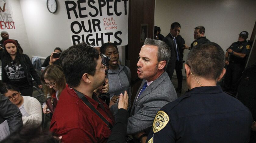 A National City police lieutenant, center right, keeps people back as police escort an activist out of the council chambers after she spoke about the death of Earl McNeil past the time limit on public comments at a City Council meeting on June 19.
