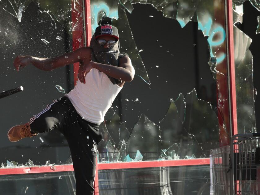 A man kicks out a storefront window in St. Paul, Minn.