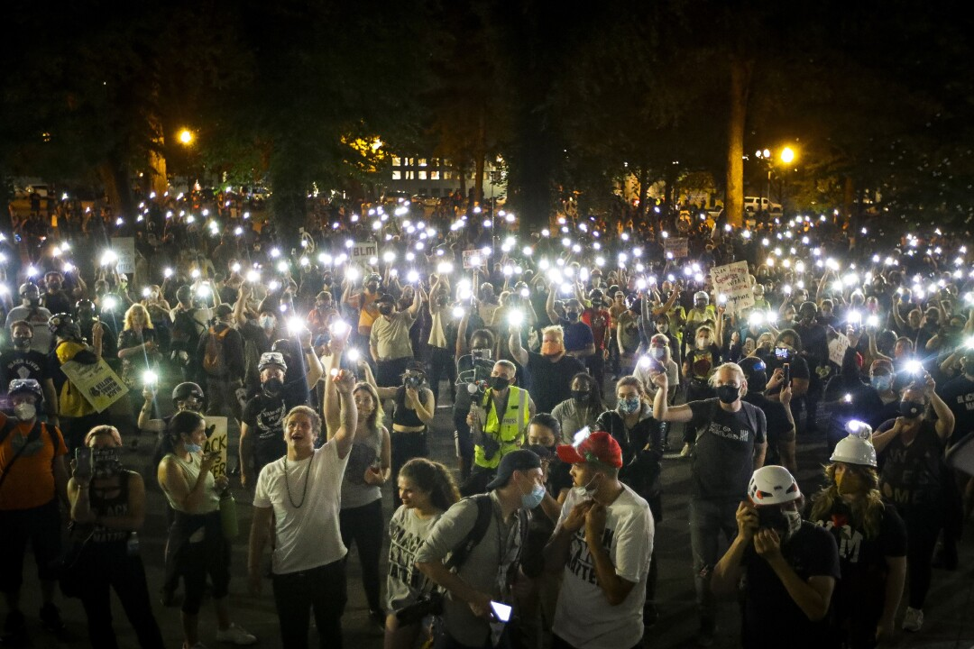 Demonstrators raise their cellphone lights as they chant and protest in Portland, Oregon