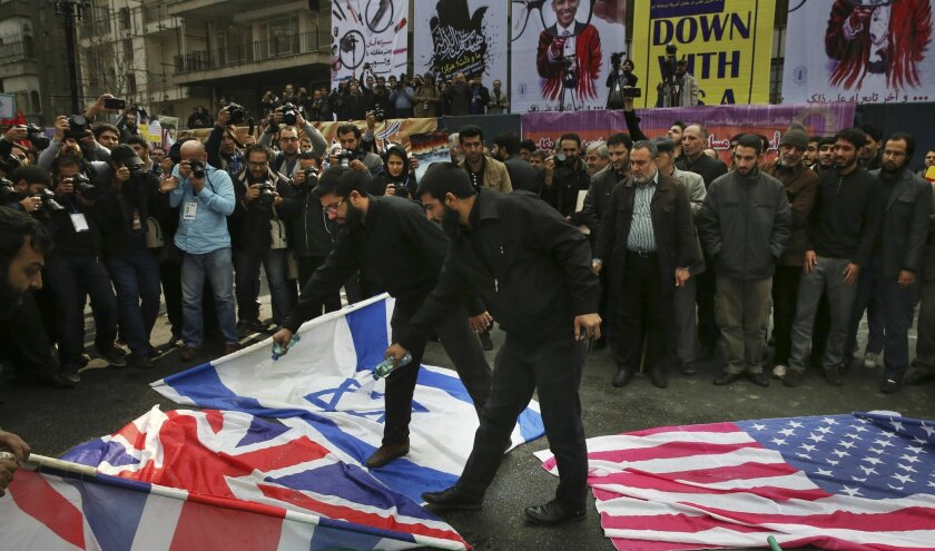 Iranian demonstrators pour gasoline on the U.S. British and Israeli flags to set on fire during an annual rally in front of the former U.S. Embassy in Tehran, marking 36th anniversary of the seizure of the embassy by militant Iranian students, Iran, Wednesday, Oct. 4, 2015. The annual state-organiz