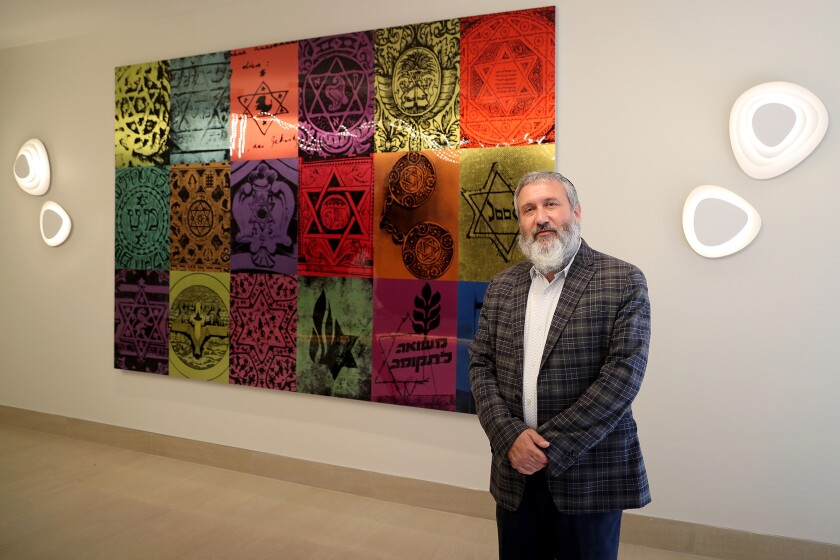 Rabbi Reuven Mintz stands in front of the History of the Star of David wall.