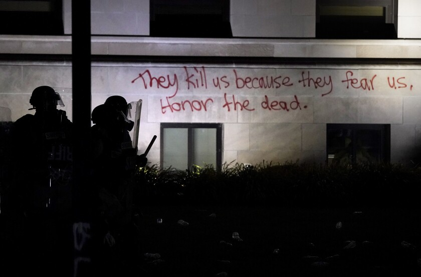 "Police line up outside Kenosha County Courthouse, spray-painted with ""They kill us because they fear us. Honor the dead."""