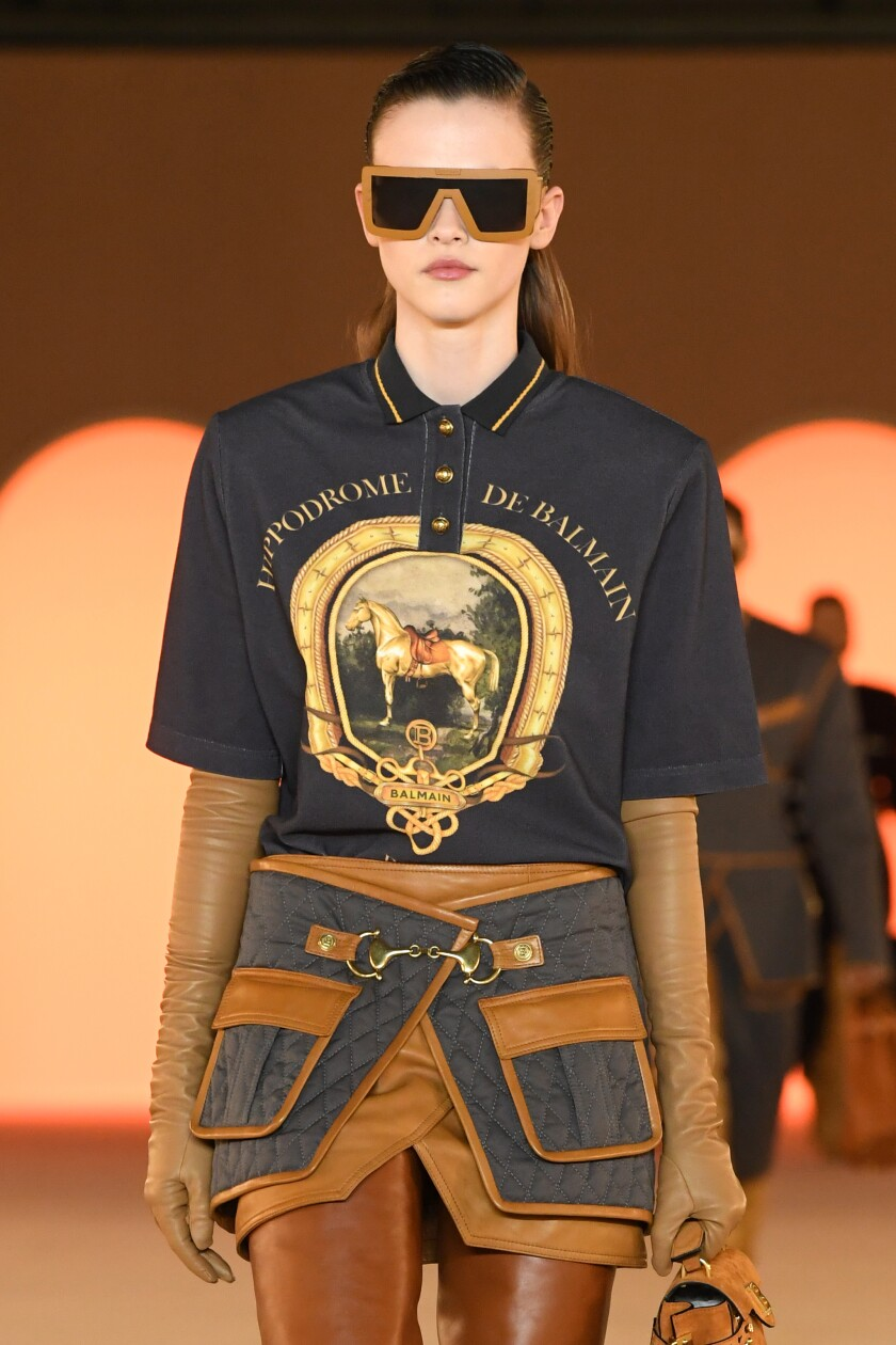 "A model wears a silk top printed with ""Hippodrome de Balmain"" and dark sunglasses."