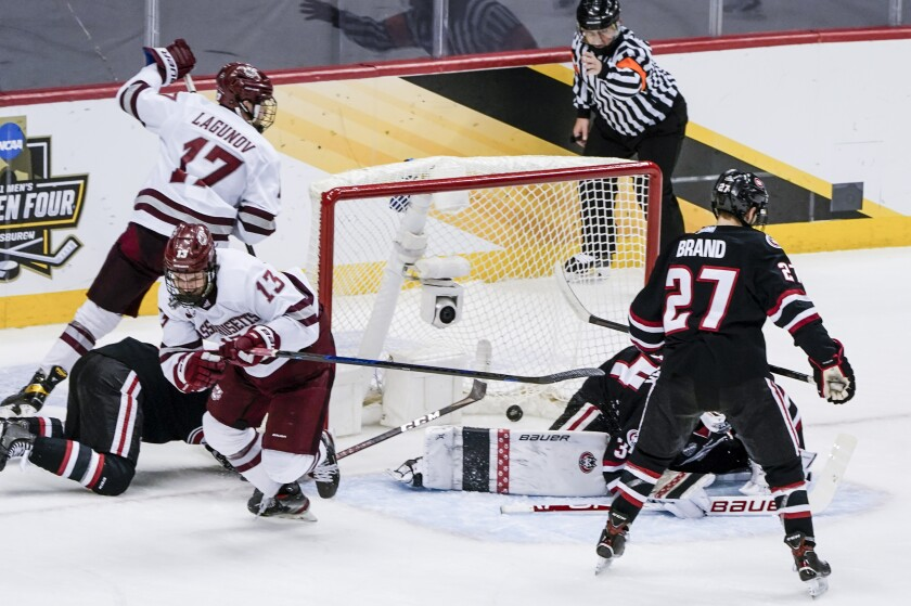 Massachusetts's Reed Lebster (13) celebrates after scoring against St. Cloud State during the first period of the NCAA men's Frozen Four hockey championship game in Pittsburgh, Saturday, April 10, 2021. (AP Photo/Keith Srakocic)