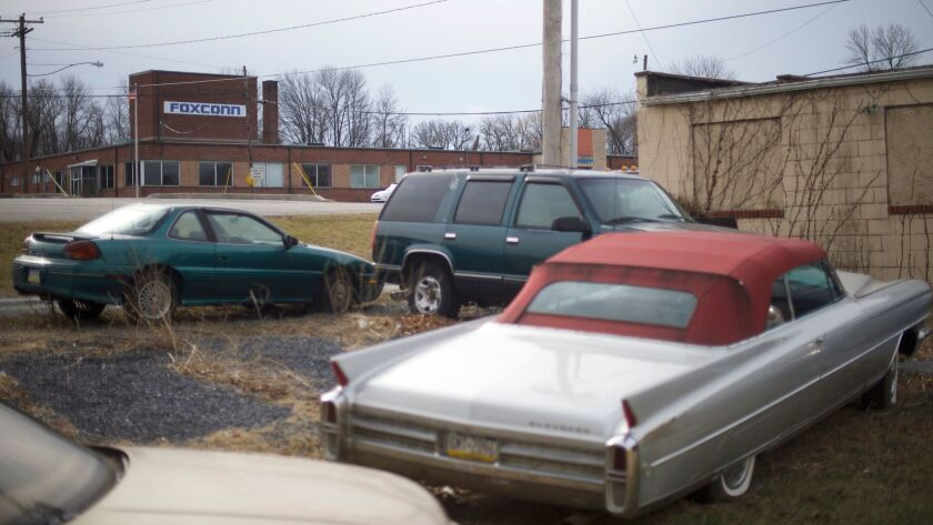 Old cars are parked across the street from the Foxconn office in Harrisburg, Pa.