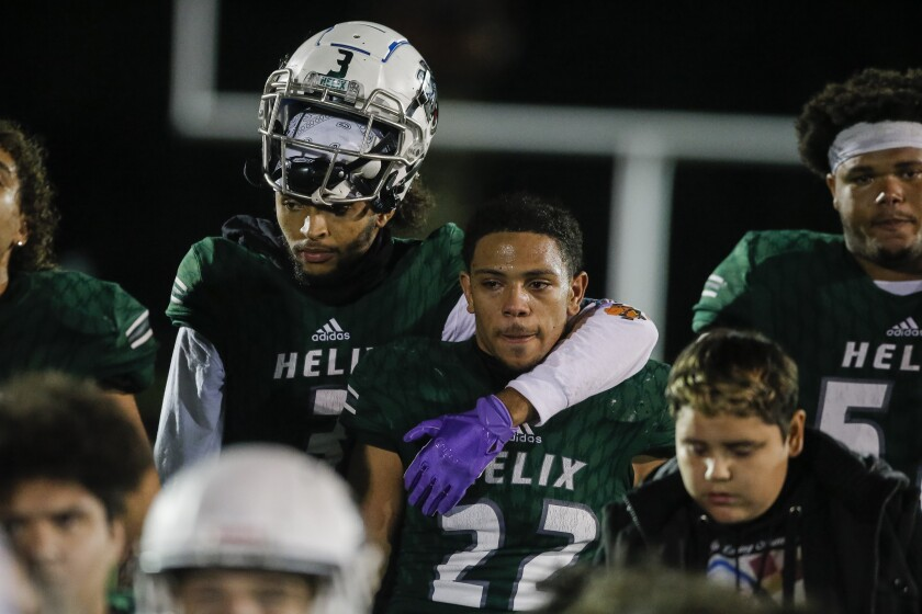 Helix teammates Jahari Hill (left) and Jeremiah Fletcher (22) comfort each other after the Highlanders were beaten by Chatsworth Sierra Canyon on Friday. Helix finished the season 11-2.