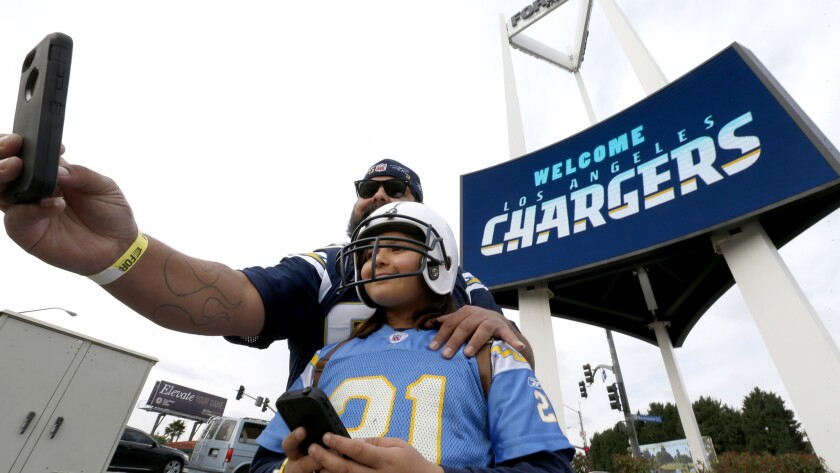 """Chargers fans Luis Salas and his daughter Lily Salas, 9, take a selfie in front of a """"Welcome Los Angeles Chargers,"""" sign at The Forum on Jan. 18."""