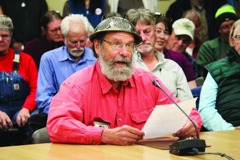 Fritz Creek area resident Barrett Fletcher gives the invocation before a Kenai Peninsula Borough Assembly meeting as a representative of the Church of the Flying Spaghetti Monster at Homer City Hall in Homer, Alaska, Tuesday, Sept. 18, 2019. A pastor wearing a spaghetti strainer on his head delivered the opening invocation at the Kenai Peninsula Borough Assembly meeting Tuesday. The invocation by the pastor of the Homer congregation of the Church of the Flying Spaghetti Monster is the second non-traditional invocation before the assembly since a court ruling. (Megan Pacer/Homer News via AP)