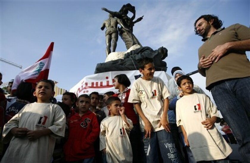 Children born to Lebanese mothers and foreign fathers gather under the Martyr's square statue as they demonstrate for Lebanese citizenship, in central Beirut, Lebanon, Friday, Oct. 10, 2008. Many Lebanese fear that allowing women to pass their citizenship to their children will upset the country's delicate sectarian balance, or open a backdoor for the large Palestinian refugee population to gain citizenship. In Lebanon, activists and women married to foreigners have in recent months held conferences and sit-ins, including protests outside the prime minister's office and near parliament in October. (AP Photo/Grace Kassab, File)