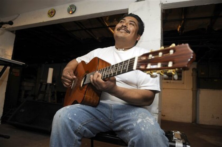 In this photo of March 24, 2011, Arnulfo Gonzalez, a Mexican Mixteco migrant, plays his guitar at the family home in the Staten Island borough of New York. A sizable number of Latin American immigrants who have settled in New York speak only indigenous languages. They speak neither English nor Spa