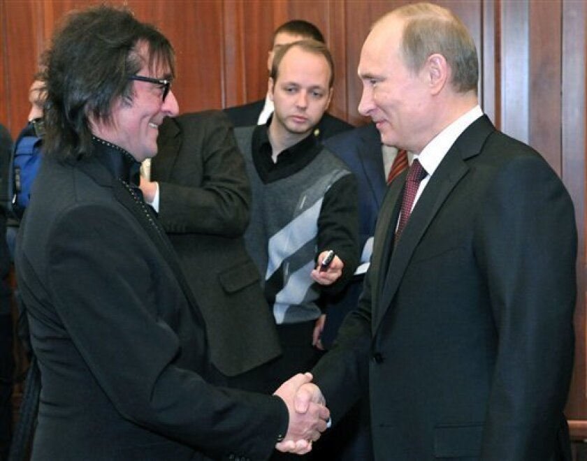 """FILE- In this Jan. 24, 2013, file photo, Russian President Vladimir Putin, right, shakes hands with famous Russian musician Yuri Bashmet on his 60th birthday, at the Kremlin in Moscow. When famed viola player Yuri Bashmet declared that he """"adored"""" President Vladimir Putin, he stirred little controversy in a country where classical musicians have often curried favor with the political elite. But political drama spilled into the orchestra pit last month when Bashmet refused to condemn a new law prohibiting Americans from adopting Russian children, and in response the beloved singer Sergei Nikitin canceled his appearance at a concert celebrating the violist's 60th birthday. (AP Photo/RIA Novosti, Alexei Nikolsky, Presidential Press Service, File)"""