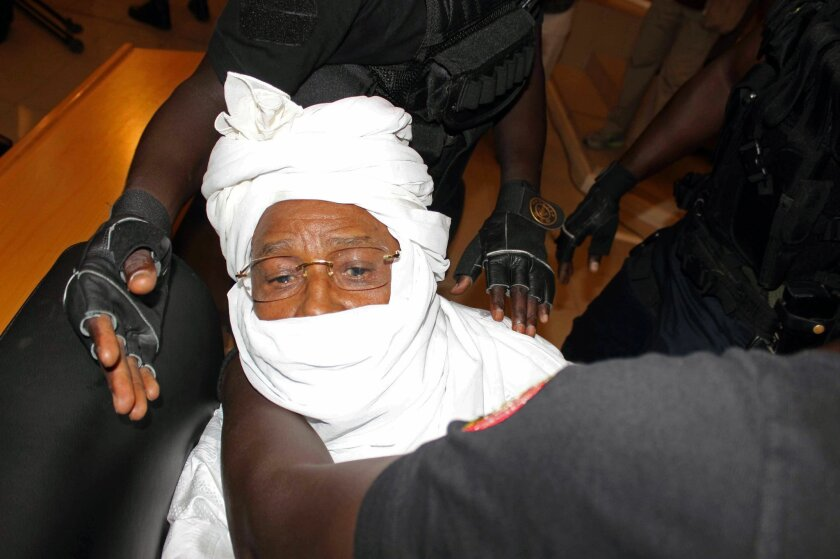 FILE- In this Monday July. 20, 2015 file photo security personnel surround former Chadian dictator Hissene Habre inside the court in Dakar, Senegal. The lawyers for Chad's ex-dictator Hissene Habre argued Thursday, Feb. 11, 2016,  against the credibility of testimonies and reports that place direct