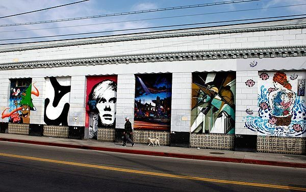 A pedestrian passes a series of murals near Mateo and 7th streets.