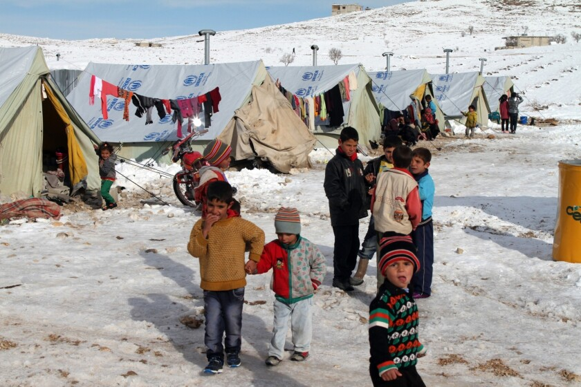 Syrian children stand in the snow in a refugee camp in the town of Arsal in Lebanon's Bekaa Valley.