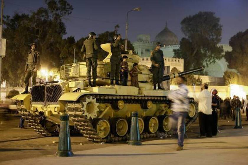 A protester takes a photo of his children next to soldiers atop an army tank Saturday outside the presidential palace in Cairo, Egypt.