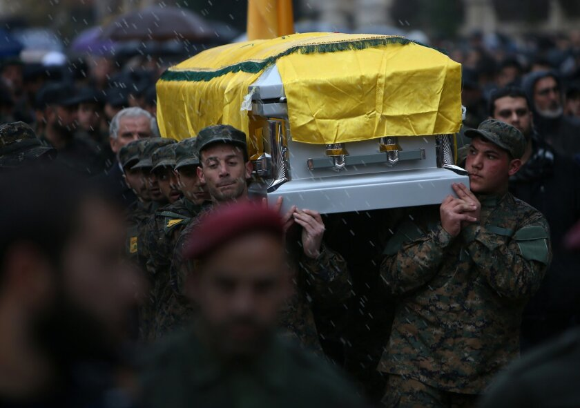 Hezbollah fighters carry the coffin of Hassan al-Laqis, a senior commander for the Lebanese militant group Hezbollah, who was gunned down outside his home, during his funeral procession at his hometown in Baalbek city, east Lebanon, Wednesday, Dec. 4, 2013. The assassination was a major breach of the Shiite militant group's security as it struggles to maintain multiple fronts while it fights alongside President Bashar Assad's forces in Syria. (AP Photo/Hussein Malla)