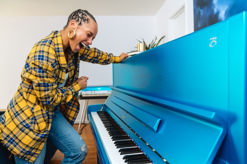 Alicia Keys is shown with the Steinway & Sons piano she is auctioning off.