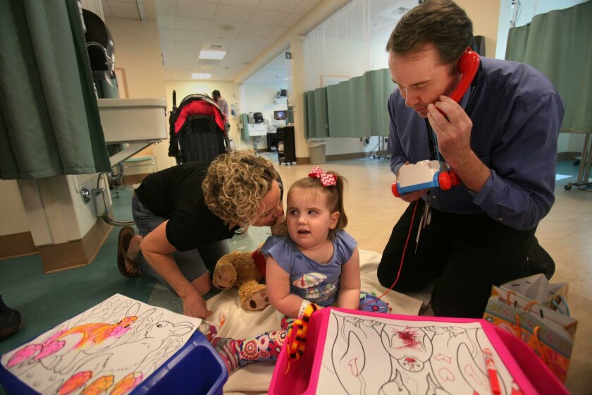 Young patient Gemma Guion, who has benefited from genetic testing on her brain tumor, listens to mother Teal Guion while Dr. John Crawford takes a make-believe call last week at Rady Children's Hospital.