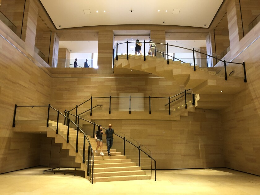 A view of a broad sandstone colored staircase that descends in a dramatic zig zag geometry