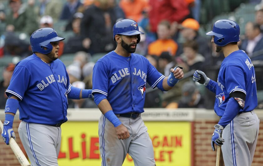Toronto Blue Jays' Dioner Navarro, left, and Jose Bautista, center, are greeted by teammate Kevin Pillar after Bautista scored on Navarro's sacrifice fly ball in the sixth inning of a home opener baseball game against the Baltimore Orioles, Friday, April 10, 2015, in Baltimore. (AP Photo/Patrick Semansky)
