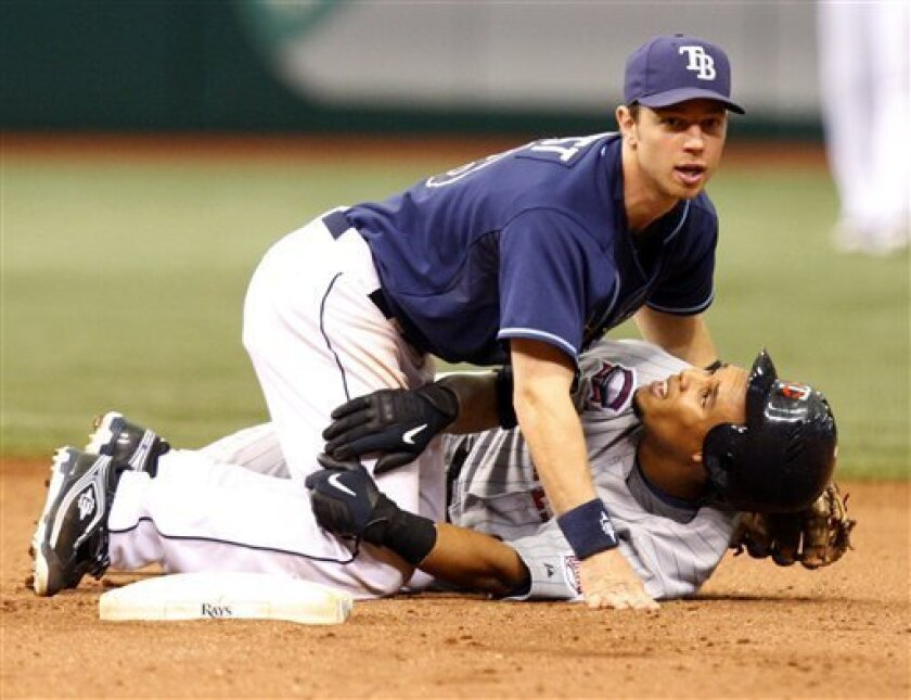 Tampa Bay Rays second baseman Ben Zobrist, top, watches his throw to first base in an attempt to complete a double play after being taken down by the slide of Minnesota Twins' Carlos Gomez during the seventh inning of a baseball game, Sunday, May 31, 2009, in St. Petersburg, Fla. (AP Photo/Mike Car