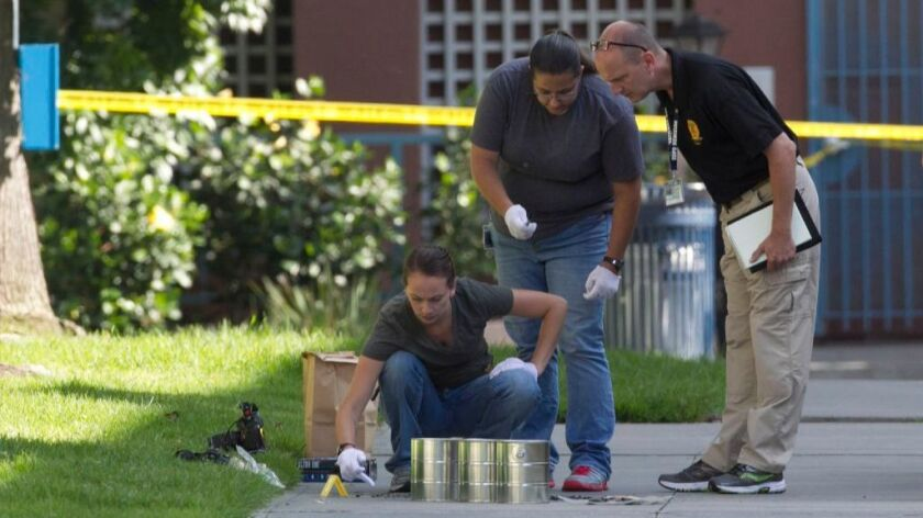 San Diego homicide investigators gather evidence from the sidewalk and grassy where Derek Vahidy was attacked.