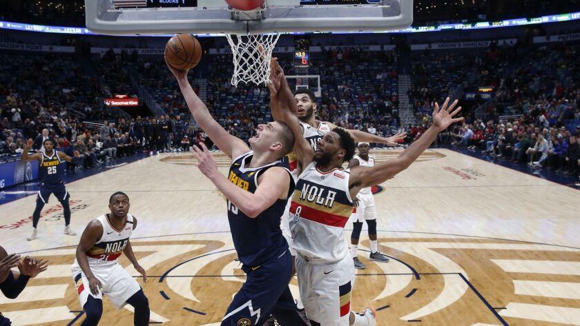 Denver Nuggets center Nikola Jokic (15) goes to the basket against New Orleans Pelicans center Jahlil Okafor (8) during the second half.