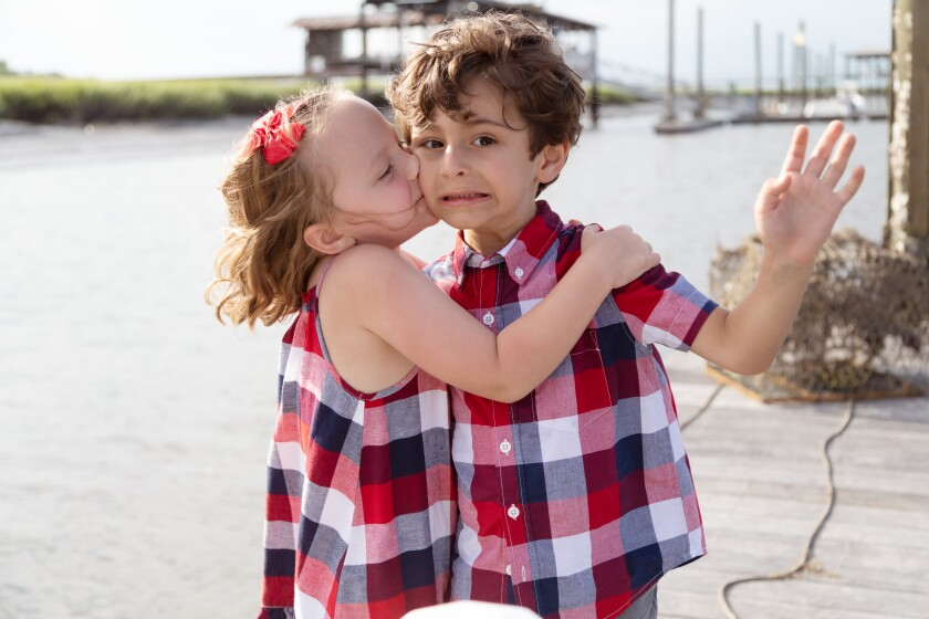 A boy and a girl embracing on the water front.