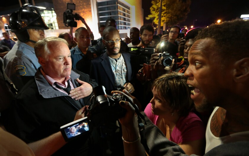 Ferguson Police Chief Thomas Jackson, left, speaks to protesters in front of the Ferguson Police Department in September.