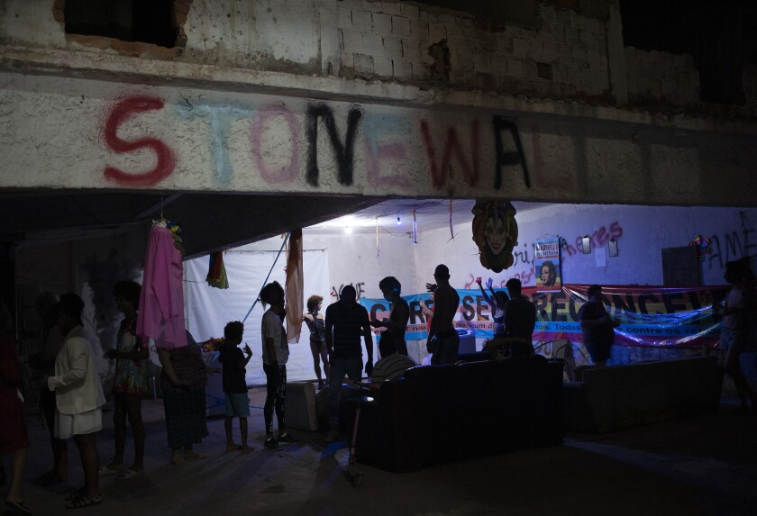 """Members of the LGBTQ community gather in the courtyard of the squat known as Casa Nem to watch the weekly presentations by residents on a makeshift stage, in Rio de Janeiro, Brazil, Saturday, May 23, 2020. """"Stonewall"""" is spray painted on an upper beam as a tribute to the Stonewall riots of 1969 in New York, the start of a rebellion that helped propel and transform the modern LGBTQ rights movement. (AP Photo/Silvia Izquierdo)"""