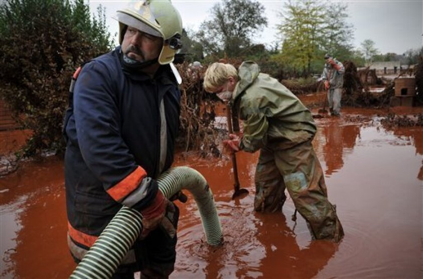 FILE - In this Oct. 6, 2010 file photo, Hungarian fire fighters clean a yard flooded by toxic mud in Devecser, Hungary. Images of homes surrounded by red mud and cars floating through toxic sludge would be unlikely in the only two U.S. two states that have facilities similar to the one in Hungary that malfunctioned, industry officials and regulators said. (AP Photo/Bela Szandelszky, File)