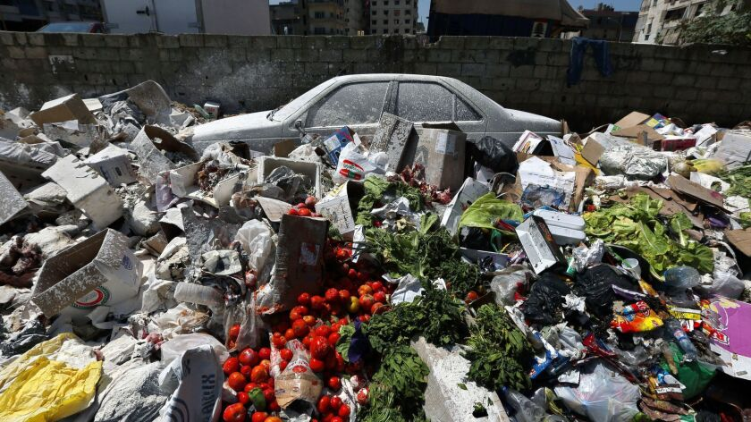 A car is seen between a pile of garbage covered with white pesticide in the Palestinian refugee camp