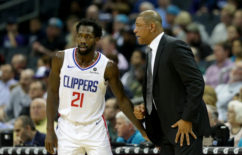 Clippers coach Doc Rivers gives some instructions to guard Patrick Beverley during a game last season.
