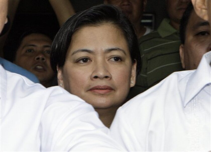 Dr. Juliet Gopez-Cervantes center, attending physician of former President Gloria Macapagal Arroyo, walks behind her security escorts after the court hearing where she was summoned to disclose Arroyo's medical condition Thursday, Dec. 1, 2011 in suburban Pasay City, south of Manila, Philippines. The court has ordered Arroyo to transfer from a private to a government-run hospital after she was arrested on electoral fraud. (AP Photo/Pat Roque)