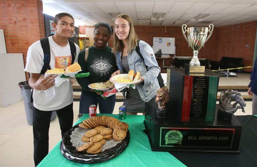 Swimmers and water polo players Trey Villapando, Sey Curry, and Angel Carlton, from left, stand next